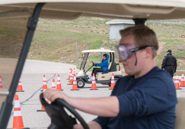Two Basalt High School students test their driving abilities while one wears drunk goggles and the other attempts to text and drive during a simulation at the school on Tuesday.