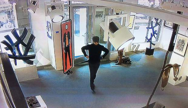 A screen shot from surveillance cameras inside an Aspen art gallery show the suspect right before he slashed a nearly $3 million painting in May 2017. An arrest warrant was issued this week for the suspect, who is from England and has family ties to the painting, according to law enforcement.