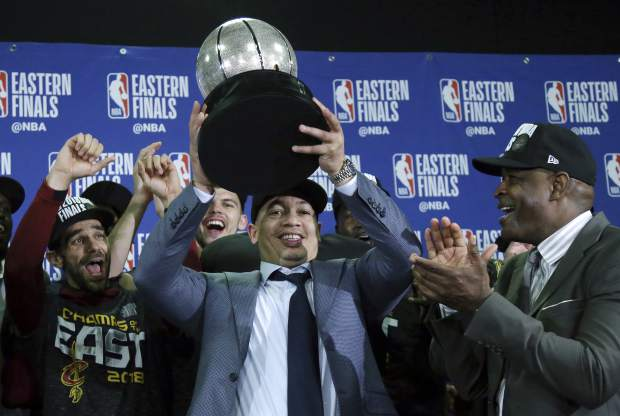 Cleveland Cavaliers head coach Tyronn Lue hoists the trophy after beating the Boston Celtics 87-79 in Game 7 of the NBA basketball Eastern Conference finals, Sunday, May 27, 2018, in Boston. (AP Photo/Elise Amendola)