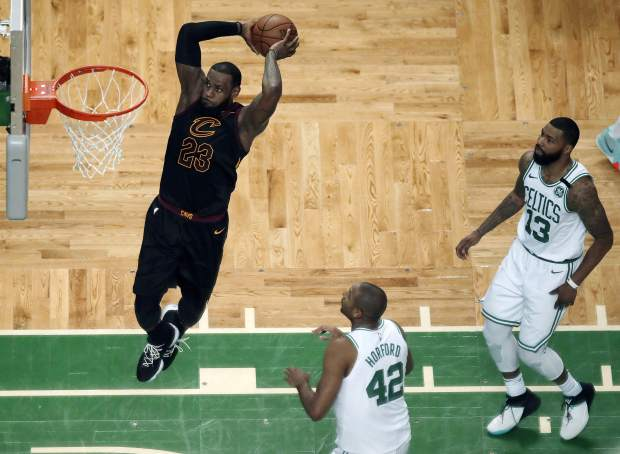 Cleveland Cavaliers forward LeBron James soars to dunk in front of Boston Celtics forward Al Horford (42) and forward Marcus Morris (13) during the first half in Game 7 of the NBA basketball Eastern Conference finals, Sunday, in Boston.