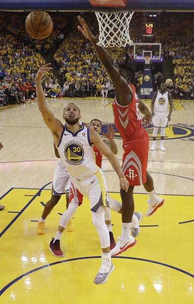 Golden State Warriors' Stephen Curry, left, drives past Houston Rockets' Clint Capela, center, during the first half in Game 3 of the NBA basketball Western Conference Finals Sunday, May 20, 2018, in Oakland, Calif. (AP Photo/Marcio Jose Sanchez)