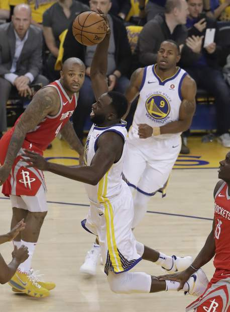 Golden State Warriors forward Draymond Green, center, shoots against the Houston Rockets during the first half of Game 3 of the NBA basketball Western Conference Finals in Oakland, Calif., Sunday, May 20, 2018. (AP Photo/Jeff Chiu)