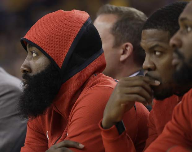 Houston Rockets guard James Harden, left, watches from the bench during the first half of Game 3 of the NBA basketball Western Conference Finals between the Golden State Warriors and the Rockets in Oakland, Calif., Sunday, May 20, 2018. (AP Photo/Marcio Jose Sanchez)