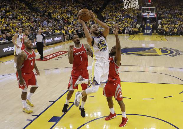 Golden State Warriors' Stephen Curry (30) drives to the basket between Houston Rockets' Chris Paul, right, and Trevor Ariza (1) during the first half in Game 3 of the NBA basketball Western Conference Finals Sunday, May 20, 2018, in Oakland, Calif. (AP Photo/Marcio Jose Sanchez)