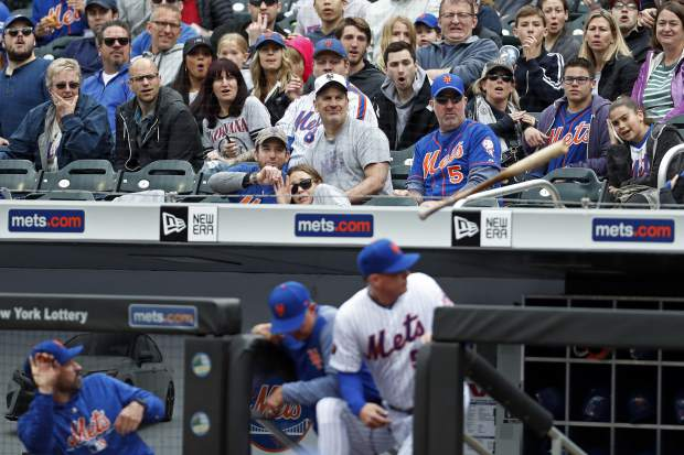 Fans react as New York Mets manager Mickey Callaway, left, Mets pitching coach Dave Eiland, center, and Mets third base coach Glenn Sherlock (53) avoid a flying bat from Colorado Rockies catcher Tony Wolters (14) during the fourth inning of a baseball game on Sunday, May 6, 2018, in New York. (AP Photo/Adam Hunger)