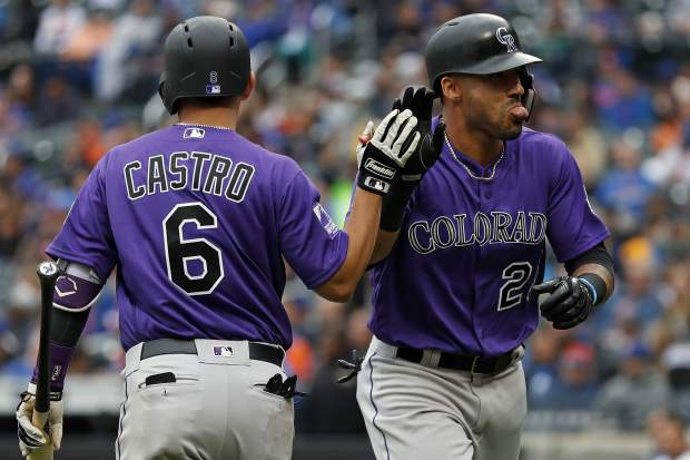 Colorado Rockies Ian Desmond (20) is congratulated by Rockies Daniel Castro (6) after hitting a solo home run during the eighth inning of a baseball game against the New York Mets on Sunday, May 6, 2018, in New York. (AP Photo/Adam Hunger)