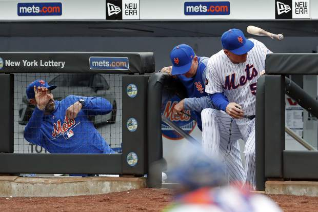 New York Mets manager Mickey Callaway, left, pitching coach Dave Eiland, center, and Mets third base coach Glenn Sherlock (53) avoid a flying bat from Colorado Rockies' Tony Wolters during the fourth inning of a baseball game on Sunday, May 6, 2018, in New York. (AP Photo/Adam Hunger)