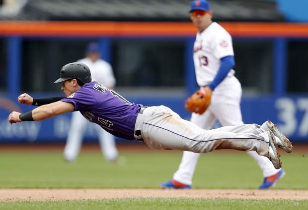 Colorado Rockies Tony Wolters (14) steals second base as New York Mets shortstop Asdrubal Cabrera looks on during the sixth inning of a baseball game on Sunday.