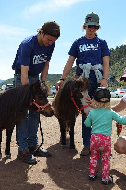 Smiling Goat Ranch volunteers introduce a tiny community member to the tiny horses.