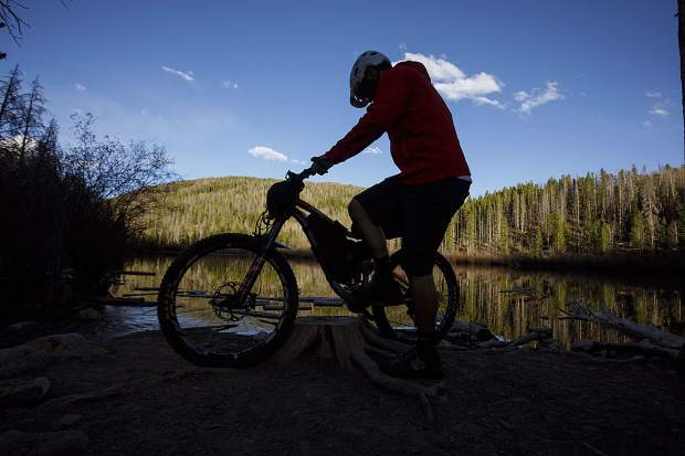 Zach Husted of Frisco demonstrates bikepacking while at Rainbow Lake on Tuesday, May 15, in Frisco. Husted went on an 11-day, 539-mile trip on and around the Colorado Trail via his mountain bike late last September.