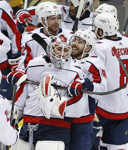 Washington Capitals goaltender Braden Holtby (70) gets a hug from Chandler Stephenson (18) during a celebration following the game-winning goal by Evgeny Kuznetsov (92) during the overtime period in Game 6 of an NHL second-round hockey playoff series against the Pittsburgh Penguins in Pittsburgh, Monday, May 7, 2018. The Capitals won the game 2-1 to take the series, four games to two. (AP Photo/Gene J. Puskar)