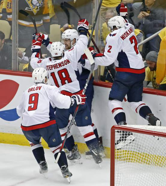 Washington Capitals' Evgeny Kuznetsov, center, celebrates his game-winning goal during the overtime period in Game 6 of an NHL second-round hockey playoff series against the Pittsburgh Penguins in Pittsburgh, Monday, May 7, 2018. The Capitals won the game, 2-1 to win the series, four games to two. (AP Photo/Gene J. Puskar)