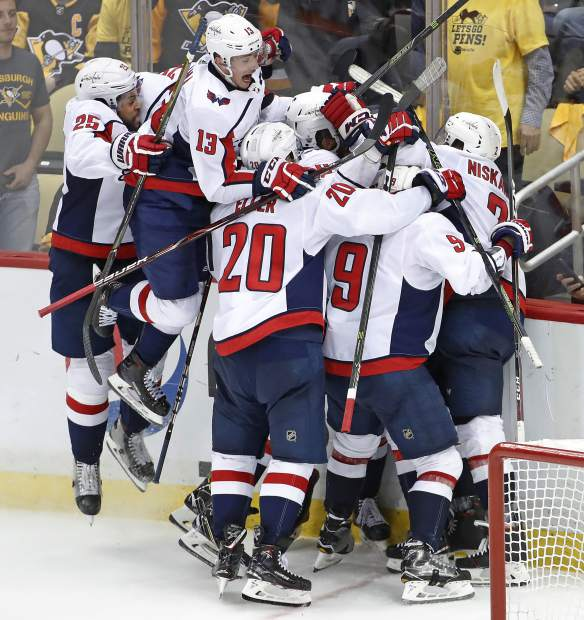 Washington Capitals left wing Jakub Vrana (13) leaps onto the pile celebrating Capitals' Evgeny Kuznetsovs' game-winning goal during the overtime period in Game 6 of an NHL second-round hockey playoff series against the Pittsburgh Penguins in Pittsburgh, Monday, May 7, 2018. The Capitals won the game, 2-1 to win the series, four games to two. AP Photo/Gene J. Puskar)