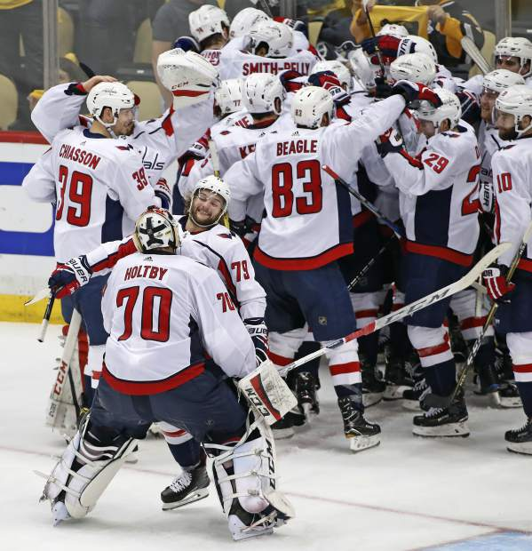 Washington Capitals goaltender Braden Holtby (70) joins the celebration with a hug from Nathan Walker (79) after Evgeny Kuznetsovs' game-winning goa during the overtime period in Game 6 of an NHL second-round hockey playoff series against the Pittsburgh Penguins in Pittsburgh, Monday, May 7, 2018. The Capitals won the game 2-1 to take the series, four games to two. AP Photo/Gene J. Puskar)