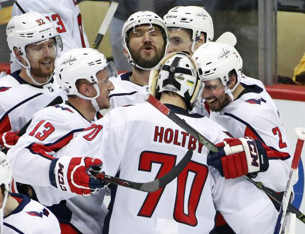 Washington Capitals goaltender Braden Holtby (70) joins the celebration of with Evgeny Kuznetsov (92), Jakub Vrana (13), Alex Ovechkin, top center, and Matt Niskanen (2) Kuznetsovs' game-winning goal during the overtime period in Game 6 of an NHL second-round hockey playoff series against the Pittsburgh Penguins in Pittsburgh, Monday, May 7, 2018. The Capitals won the game 2-1 to take the series, four games to two. AP Photo/Gene J. Puskar)