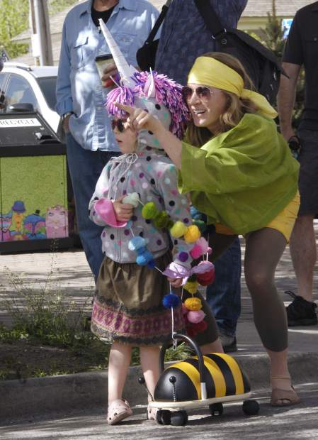 Elly Harder and daughter Luna, sporting her best unicorn look, watch the Parade of the Species during Dandelion Day in Carbondale Saturday.
