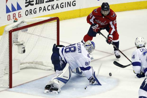 Washington Capitals center Evgeny Kuznetsov (92), from Russia, looks for the puck as Tampa Bay Lightning goaltender Andrei Vasilevskiy (88), from Russia, blocks a shot during the second period of Game 6 of the NHL Eastern Conference finals hockey playoff series, Monday, May 21, 2018, in Washington. (AP Photo/Alex Brandon)
