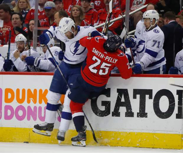 Tampa Bay Lightning defenseman Victor Hedman (77) and Washington Capitals right wing Devante Smith-Pelly (25) crash into the boards chasing a loose puck during the first period of Game 6 of the NHL Eastern Conference finals hockey playoff series, Monday, May 21, 2018, in Washington. (AP Photo/Pablo Martinez Monsivais)