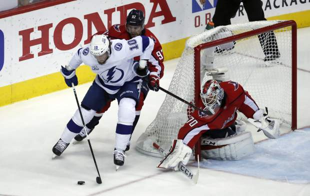 Tampa Bay Lightning center J.T. Miller (10) skates with Washington Capitals center Evgeny Kuznetsov (92), from Russia, behind him, with Washington Capitals goaltender Braden Holtby (70) in the net, during the first period of Game 6 of the NHL Eastern Conference finals hockey playoff series, Monday, May 21, 2018, in Washington. (AP Photo/Alex Brandon)