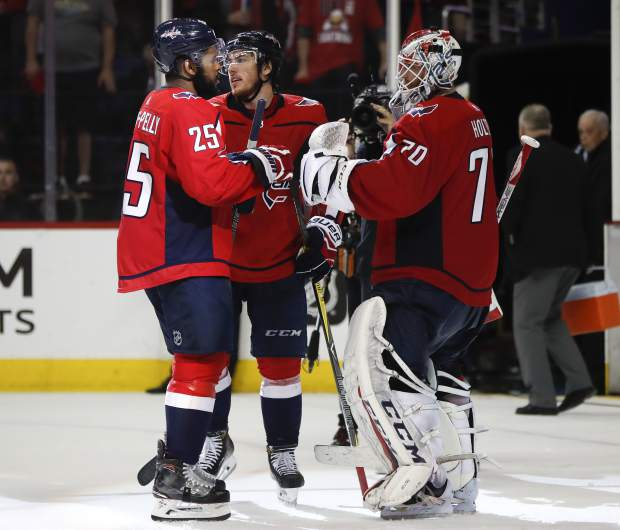 Washington Capitals' Devante Smith-Pelly (25), T.J. Oshie (77) and goaltender Braden Holtby (70) celebrate at the end of Game 6 of the NHL Eastern Conference finals hockey playoff series, Monday, May 21, 2018, in Washington. Capitals won 3-0. (AP Photo/Pablo Martinez Monsivais)