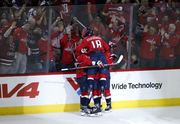 Washington Capitals center Chandler Stephenson (18) jumps into the the crowd of his teammates as they celebrate a goal by right wing Devante Smith-Pelly (25) during the third period of Game 6 of the NHL Eastern Conference finals hockey playoff series against the Tampa Bay Lightning, Monday, May 21, 2018, in Washington. The Capitals won 3-0. (AP Photo/Alex Brandon)