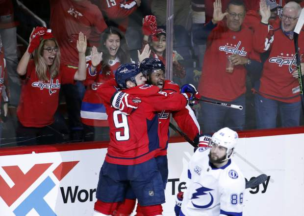 Washington Capitals defenseman Dmitry Orlov (9), from Russia, and right wing Devante Smith-Pelly (25) celebrate Smith-Pelly's goal with Tampa Bay Lightning right wing Nikita Kucherov (86), from Russia, nearby during the third period of Game 6 of the NHL Eastern Conference finals hockey playoff series, Monday, May 21, 2018, in Washington. The Capitals won 3-0. (AP Photo/Alex Brandon)