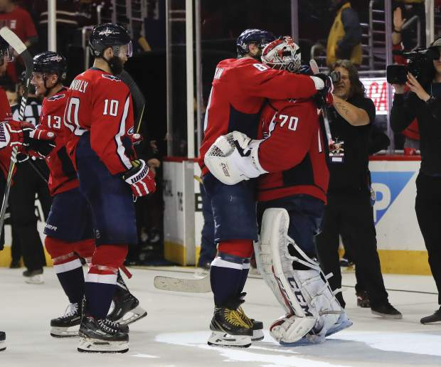 Washington Capitals left wing Alex Ovechkin (8), from Russia hugs Capitals' goaltender Braden Holtby (70) at the end of Game 6 of the NHL Eastern Conference finals hockey playoff series against the Tampa Bay Lightning, Monday, May 21, 2018, in Washington. Looking on is Washington Capitals right wing Brett Connolly (10) as the Capitals won 3-0. (AP Photo/Pablo Martinez Monsivais)