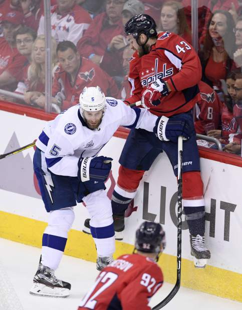 Washington Capitals right wing Tom Wilson (43) hits the boards next to Tampa Bay Lightning defenseman Dan Girardi (5) during the first period of Game 4 of the NHL hockey Eastern Conference finals Thursday, May 17, 2018 in Washington. (AP Photo/Nick Wass)
