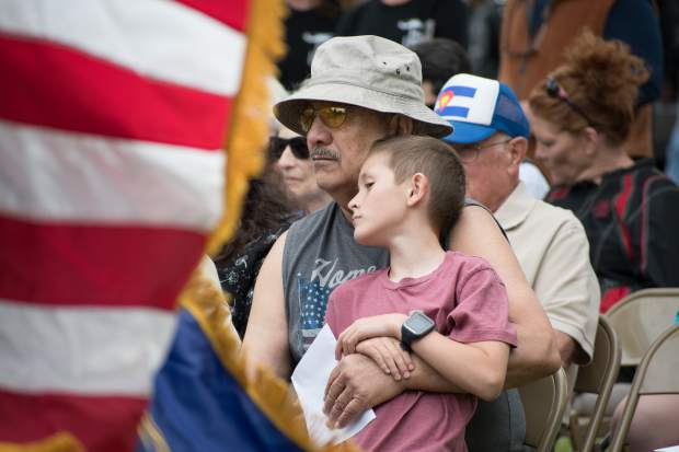 Dennis Dupoint and his great-grandson Colter Vanginkel, 8, listen to speakers during Monday's Memorial Day Ceremony at Rosebud Cemetery.