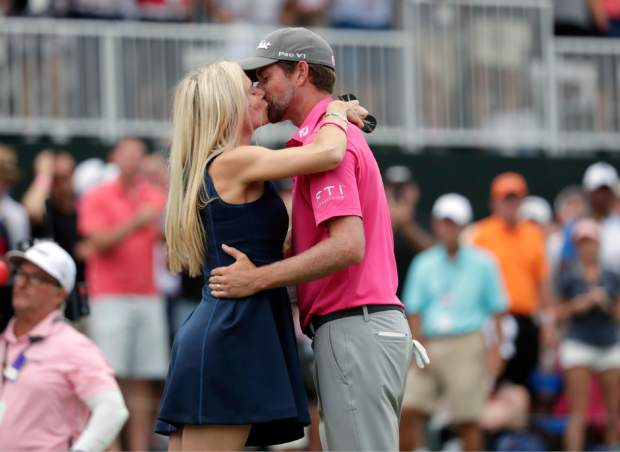 Webb Simpson kisses his wife Taylor Dowd Simpson after winning The Players Championship golf tournament Sunday, May 13, 2018, in Ponte Vedra Beach, Fla. (AP Photo/Lynne Sladky)