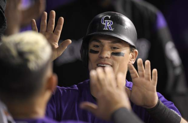 Colorado Rockies' Tony Wolters, right, is congratulated by Gerardo Parra after scoring on a single by Carlos Gonzalez during the eighth inning of a baseball game against the Los Angeles Dodgers, Monday, May 21, 2018, in Los Angeles. (AP Photo/Mark J. Terrill)