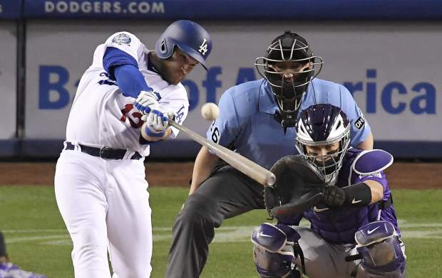 Los Angeles Dodgers' Max Muncy, left, hits a solo home run as Colorado Rockies catcher Tony Wolters, right, watches along with home plate umpire Ryan Blakney during the fourth inning of a baseball game Monday, May 21, 2018, in Los Angeles. (AP Photo/Mark J. Terrill)