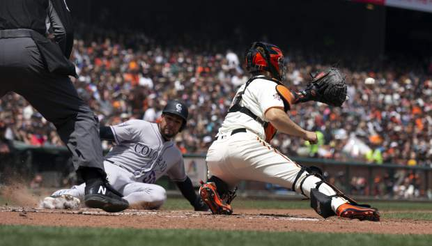 San Francisco Giants catcher Nick Hundley, right, prepares to put the tag on Colorado Rockies Noel Cuevas (56) who was trying to score on a double by Pat Valaika during the fourth inning, Sunday.