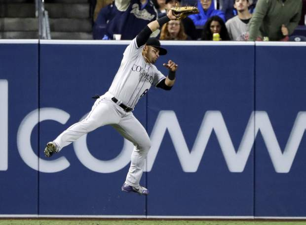Colorado Rockies left fielder Gerardo Parra makes a leaping catch for the out on the San Diego Padres' Manuel Margot during the fifth inning of a baseball game Monday, May 14, 2018, in San Diego. (AP Photo/Gregory Bull)