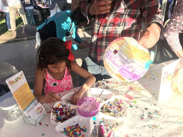 Ella Neppl, 5, concentrates on a craft project at the Handmakery booth during Carbondale's family block party Friday. Ella and Jonathan Neppl live in New Castle, and Jonathan said this was their first time at Carbondale's First Friday.