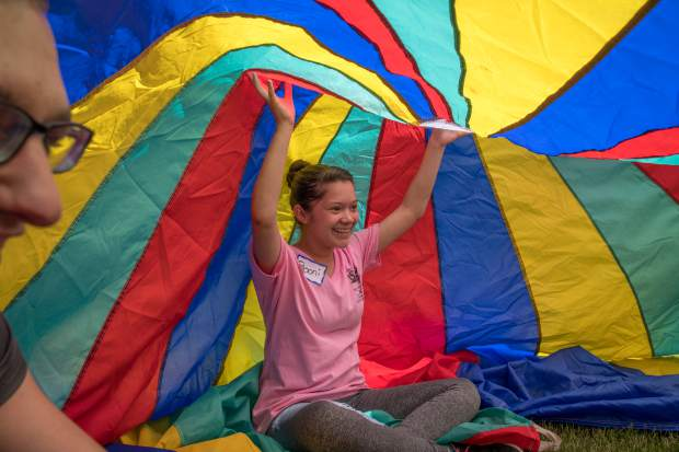 Miss Strawberry Days contestant Eboni Archila plays a parachute game with Mountain Valley Developmental Services clients during Thursday's field day.