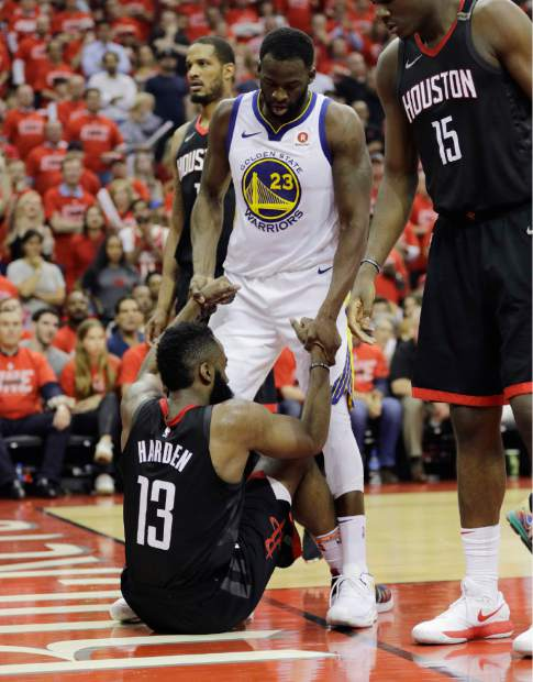Golden State Warriors forward Draymond Green (23) helps Houston Rockets guard James Harden (13) after he fell to the floor during the second half in Game 7 of the NBA basketball Western Conference finals, Monday, May 28, 2018, in Houston. (AP Photo/David Phillip)