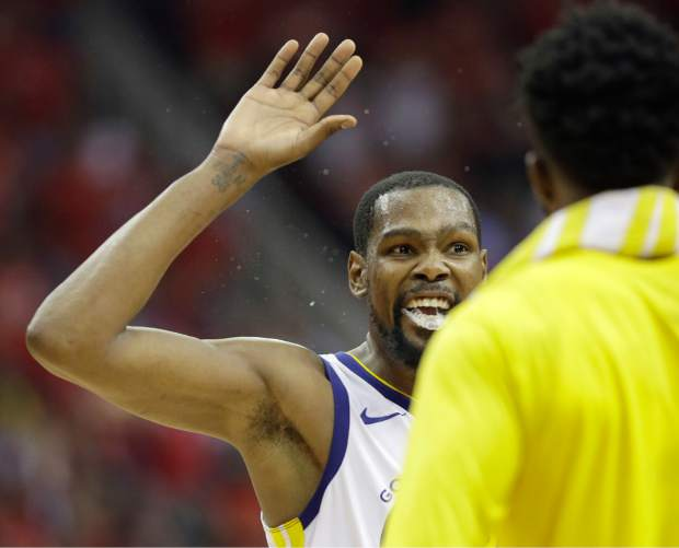 Golden State Warriors forward Kevin Durant, left, celebrates with teammates during the second half in Game 7 of the NBA basketball Western Conference finals against the Houston Rockets, Monday, May 28, 2018, in Houston. (AP Photo/David J. Phillip)