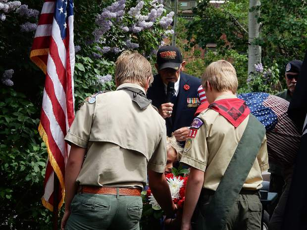Members of the local troops of Scouts work with Marine Corps veteran Dick Merritt on the Laying of the Memorial Wreath at Aspen's Memorial Day Observance on Monday.