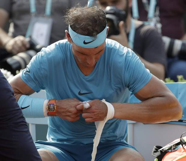 Spain's Rafael Nadal removes a bandage on his wrist in the men's final match of the French Open tennis tournament against Austria's Dominic Thiem at the Roland Garros stadium in Paris, France, Sunday, June 10, 2018. (AP Photo/Alessandra Tarantino)