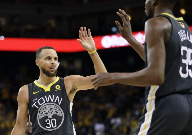 Golden State Warriors guard Stephen Curry (30) celebrates with forward Kevin Durant during the first half of Game 2 of basketball's NBA Finals against the Cleveland Cavaliers in Oakland, Calif., Sunday, June 3, 2018. (AP Photo/Marcio Jose Sanchez)