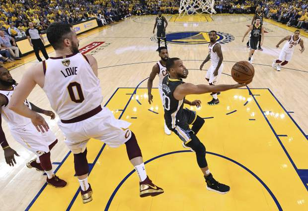 Golden State Warriors guard Stephen Curry, right, shoots against Cleveland Cavaliers forward Kevin Love (0) during the first half of Game 2 of basketball's NBA Finals in Oakland, Calif., Sunday, June 3, 2018. (Kyle Terada/Pool Photo via AP)