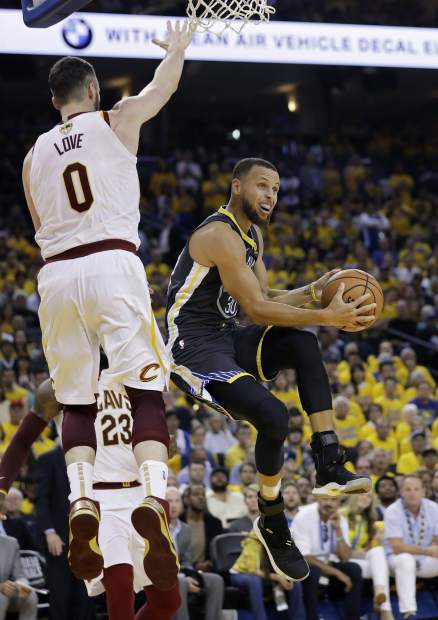 Golden State Warriors guard Stephen Curry, right, shoots against Cleveland Cavaliers forward Kevin Love (0) during the first half of Game 2 of basketball's NBA Finals in Oakland, Calif., Sunday, June 3, 2018. (AP Photo/Marcio Jose Sanchez)