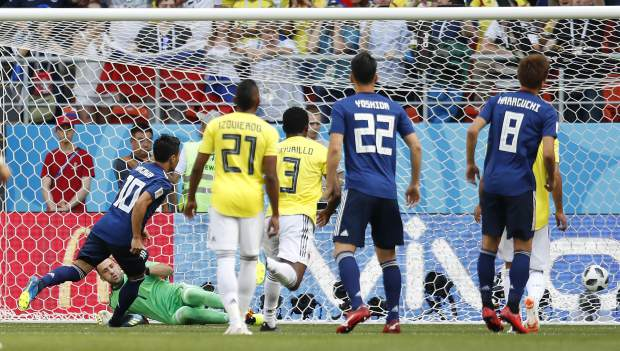 Japan's Shinji Kagawa, left, scores the opening goal during the group H match between Colombia and Japan at the 2018 soccer World Cup in the Mordavia Arena in Saransk, Russia, Tuesday, June 19, 2018. (AP Photo/Natacha Pisarenko)