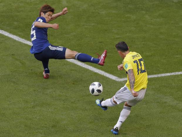 Japan's Yuya Osako, left, tries to block a shot by Colombia's James Rodriguez, right, during the group H match between Colombia and Japan at the 2018 soccer World Cup in the Mordavia Arena in Saransk, Russia, Tuesday, June 19, 2018. (AP Photo/Vadim Ghirda)