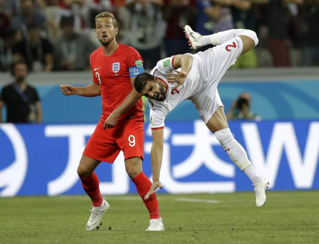 Tunisia's Syam Ben Youssef, right, jumps as he fights for the ball with England's Harry Kane during the group G match between Tunisia and England at the 2018 soccer World Cup in the Volgograd Arena in Volgograd, Russia, Monday, June 18, 2018. (AP Photo/Sergei Grits)