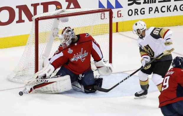 Washington Capitals goaltender Braden Holtby, left, turns the puck away as Vegas Golden Knights forward Jonathan Marchessault (81) closes in during the first period in Game 4 of the NHL hockey Stanley Cup Final, Monday, June 4, 2018, in Washington. (AP Photo/Pablo Martinez Monsivais)