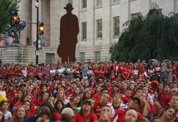 Washington Capitals fans watch Game 4 of the NHL hockey Stanley Cup Final between the Washington Capitals and the Vegas Golden Knights, Monday, June 4, 2018, outside Capital One Arena in Washington. The National Portrait Galley is in the background (AP Photo/Carolyn Kaster)