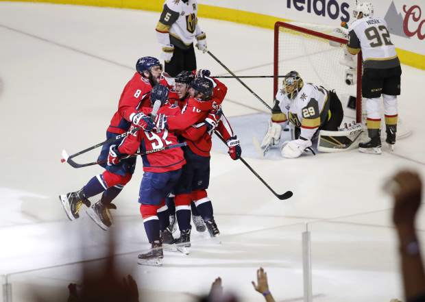 Teammates celebrate with Washington Capitals forward T.J. Oshie, center of the huddle, who scored a goal past Vegas Golden Knights goaltender Marc-Andre Fleury (29) during the first period in Game 4 of the NHL hockey Stanley Cup Final, Monday, June 4, 2018, in Washington. (AP Photo/Pablo Martinez Monsivais)