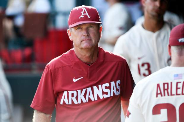 FILE - In this June 11, 2018, file photo, Arkansas coach Dave Van Horn is shown in the dugout before the Razorbacks game against South Carolina at an NCAA college baseball tournament super regional baseball game in Fayetteville, Ark. Arkansas will make its ninth College World Series appearance this weekend, the school's fifth in 16 seasons under coach Dave Van Horn. The Razorbacks believe it's time they finally won their first national championship. (AP Photo/Michael Woods, File)